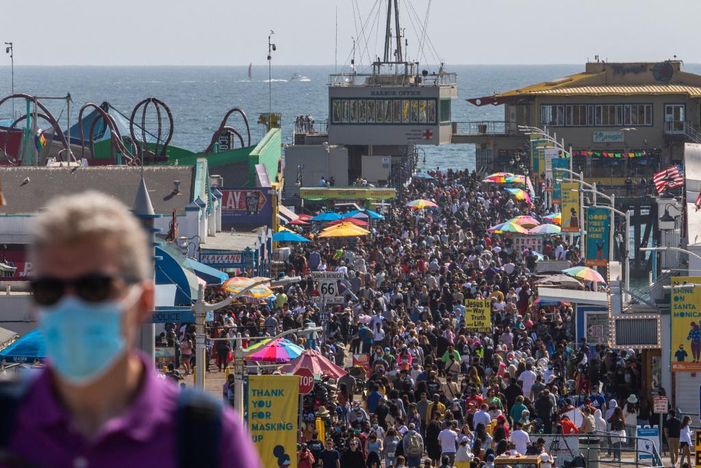 People walk through the Santa Monica pier ahead of Memorial Day in Santa Monica, California on May 29, 2021.