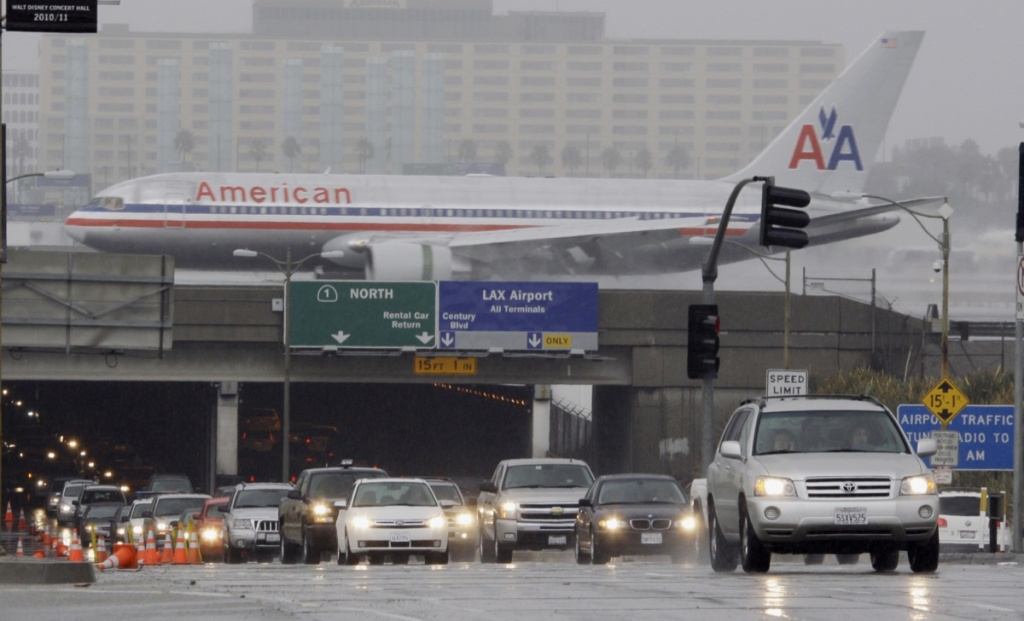 File: Traffic through the Sepulveda Boulevard tunnel under Los Angeles International Airport is backed up as a lane is closed due to flooding while an airliner lands, as rain falls on a large part of Southern California Wednesday, Oct. 6, 2010.