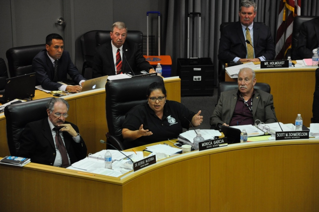 FILE - Los Angeles Unified School Board member Mónica García (center) speaks during a meeting, as colleagues George McKenna (left), Scott Schmerelson (right) and district staff (rear) listen.