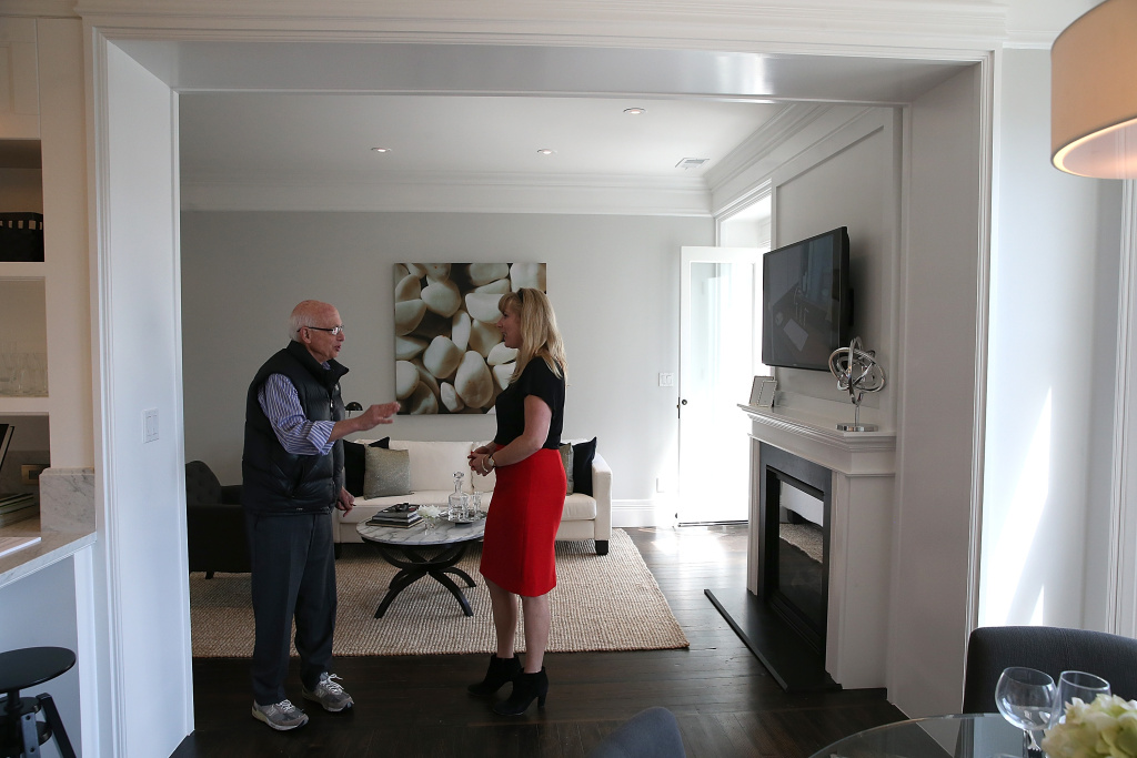 Real estate agent Katie Hayes (R) answers questions about a home for sale during an open house on May 28, 2013 in San Francisco, California.