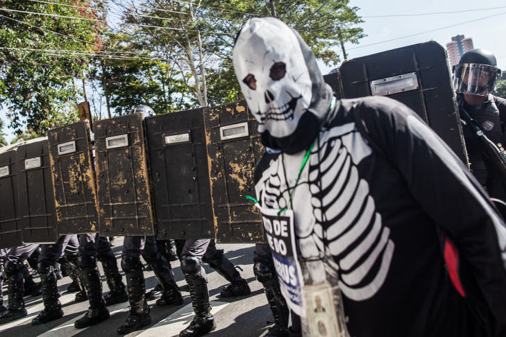 A protester is detained by police during a demonstration by people demanding better public services and against the money spent on the World Cup soccer tournament in Sao Paulo, Brazil, Thursday, June 12, 2014. Brazilian police clashed with anti-World Cup protesters trying to block part of the main highway leading to the stadium that hosts the opening match of the tournament.