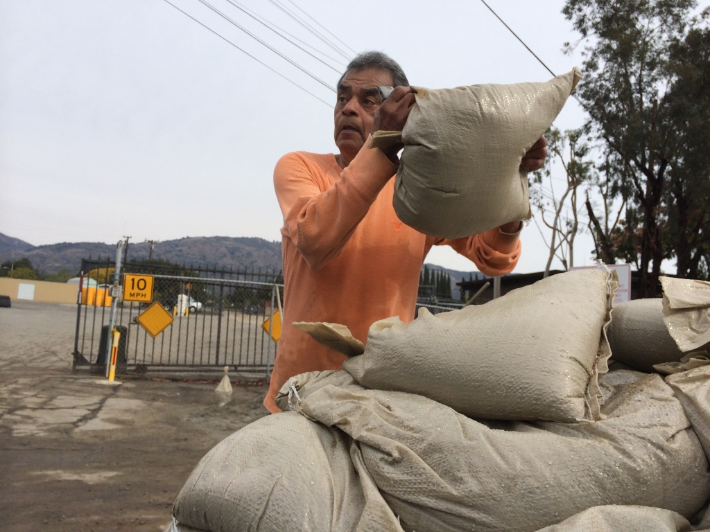 George Rodriguez, 69, a volunteer, loads sandbags at the Glendora City Yard in preparation for a rainstorm.