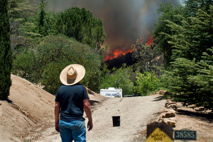 Local residents watch as winds carry the Powerhouse Fire through the mountains. The blaze was first reported on Thursday afternoon, and burned through the night.