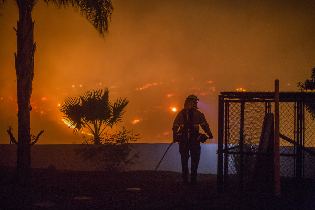 A firefighter guards a house at the Lilac Fire on December 7, 2017 near Bonsall, California.