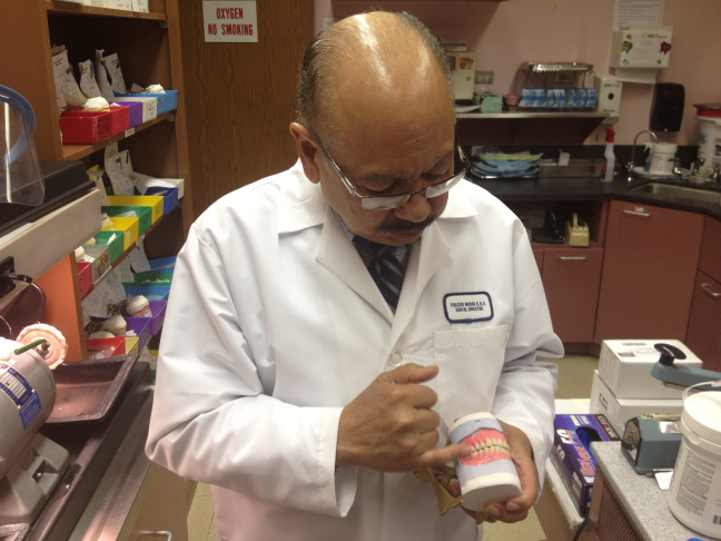 Dr. Frazier Moore, Watts Health Center's dental director, points to a molar on a full set of dentures. Last year, Watts' dental wing doled out 470 sets of dentures.