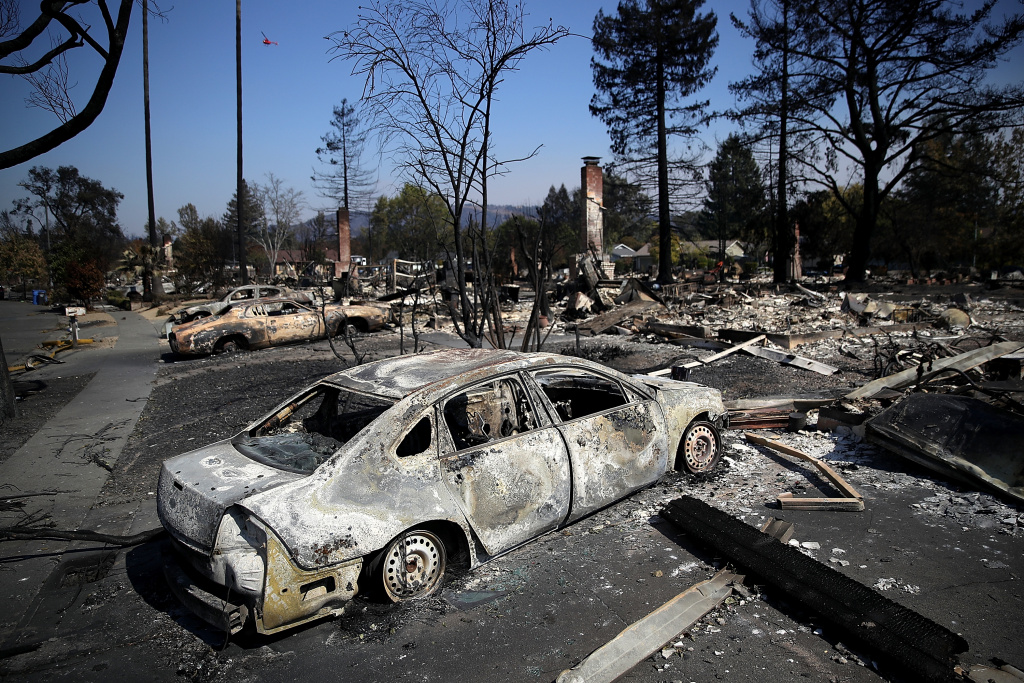 Burned cars sit in front of homes that were destroyed by the Tubbs Fire on October 12, 2017 in Santa Rosa, California.