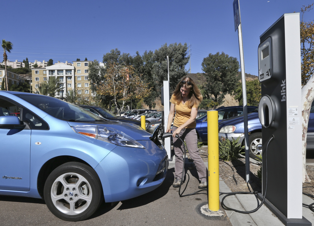 Angie Vorhies plugs in the charging cord to her Nissan Leaf electric vehicle at a San Diego mall in November 2013.