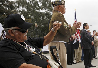 Veteran J.J. Asevedo raises a clenched fist at a news conference to announce a lawsuit against the federal government, alleging the misuse a 390-acre plot of land in West Los Angeles that was donated some 130 years ago to house veterans who need care after traumatic military experiences, at the Los Angeles Veterans Administration center in Los Angeles Wednesday, June 8, 2011.