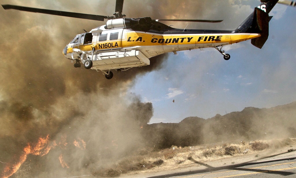 A helicopter from the L.A. County Fire Department provides air support to crews battling the La Tuna Fire burns in the hills above Burbank on September 2, 2017.