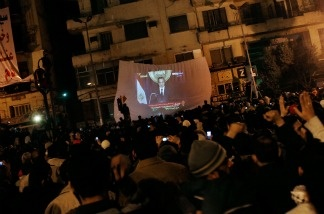 Protesters watch Egyptian president Hosni Mubarek give a speech on a projected television screen in Tahrir Square on Feb. 1, 2011 in Cairo, Egypt. In a pre-recorded televised address to the country, President Mubarak announced that he would not run for another term in office.
