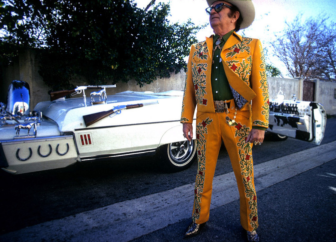 Nudie Cohn posing in front of one of his custom Nudie Mobiles, a Pontiac Bonneville convertible made for Hank Williams Jr.