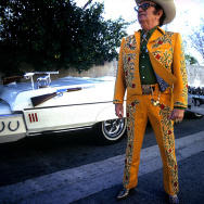 Nudie Cohn posing in front of one of his custom Nudie Mobiles, a Cadillac El Dorado made for his wife, Bobbie.