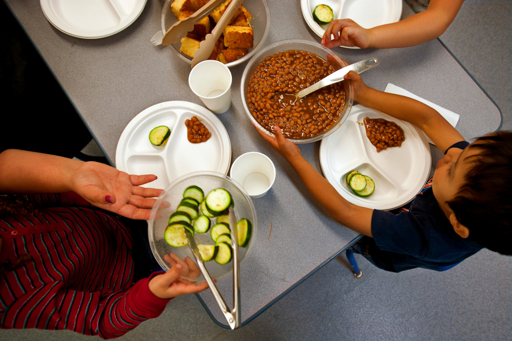 Kids pass food around the table for lunch.
