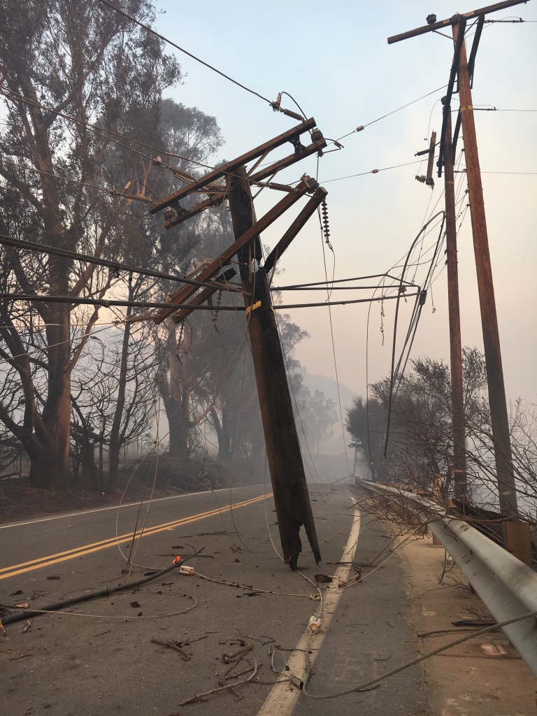 A burned-through utility pole hangs precariously over Highway 150 about a quarter mile from the origin of the Thomas Fire, near Thomas Aquinas College on Dec. 6, 2017.