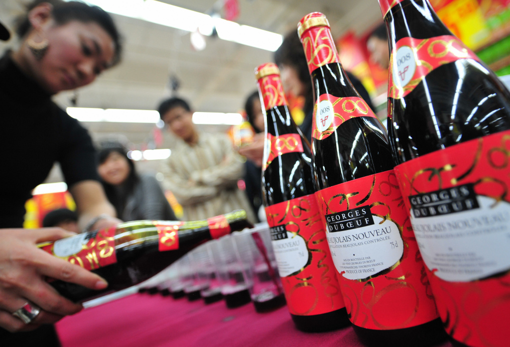 A bartender serves Chinese wine connoisseurs the newly released French Beaujolais Nouveau in Beijing.