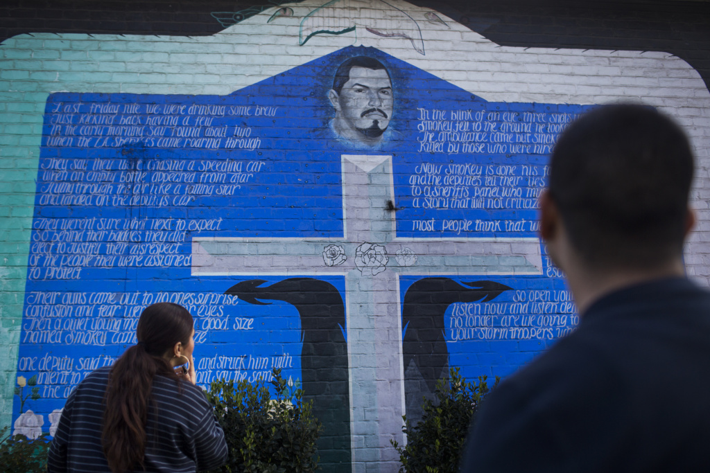 Amanda Gutierrez, left, and Eddie Licon look at a mural in Ramona Gardens in Boyle Heights memorializing a community member killed by police in the 1990s.