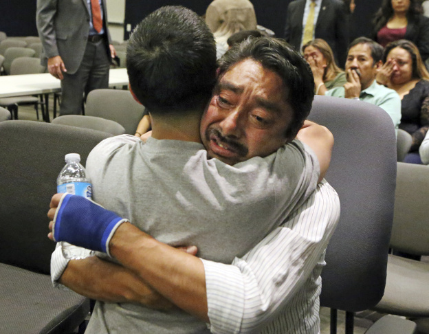 Fernando Duran, right, father of murder victim Bree'Anna Guzman, embraces an unidentified man as the Los Angeles Police Department announces the arrest of a suspect in the 2011 kidnapping and murders of two young women, at police headquarters in downtown Los Angeles Tuesday, May 30, 2017.