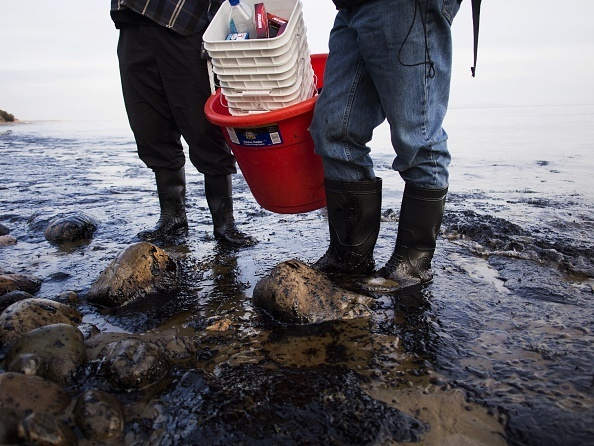 Officials walk along an the oil-covered beach north of Goleta, California. Initial estimates put the spill at about 21,000 gallons.