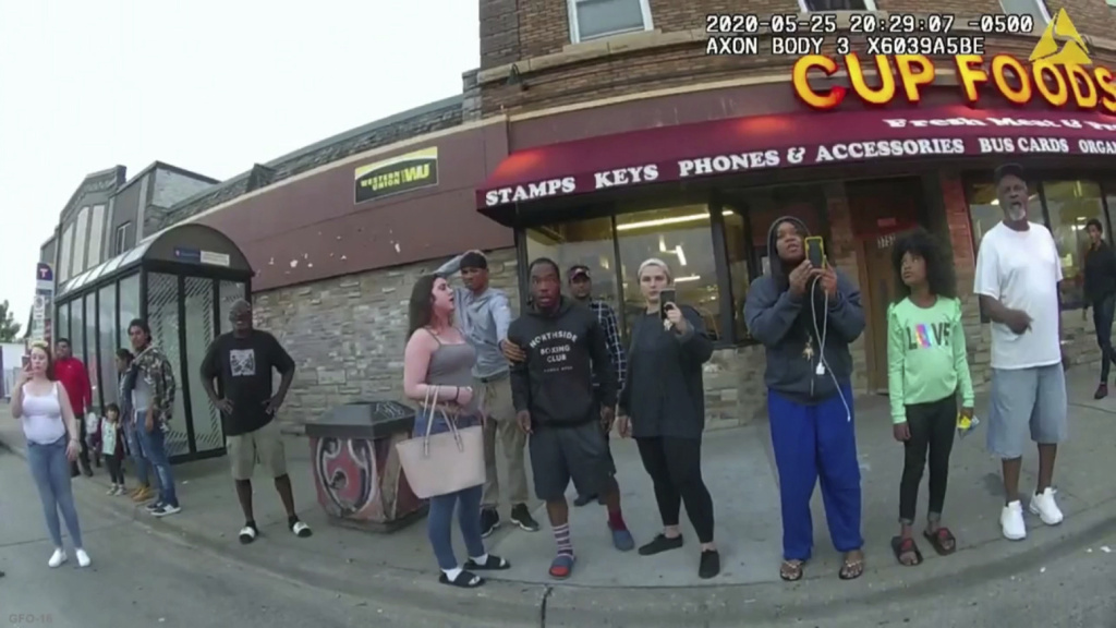 A police body camera image shows bystanders including Darnella Frazier (third from right filming) as former Minneapolis police officer Derek Chauvin was recorded pressing his knee on George Floyd's neck in Minneapolis.