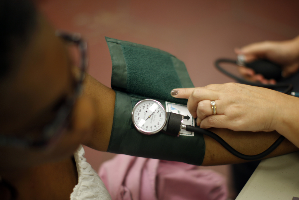 A nurse checks the blood pressure of a patient as nurses and physicians give free basic health screenings on July 10, 2012 in Los Angeles, California. Despite the debates over the Affordable Care Act that have caused a government shutdown, part of Obamacare started today when the online healthcare exchange market opened.