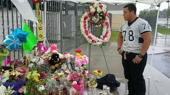 A memorial at South Gate High School for Cindi Santana, 17, who was fatally stabbed by her boyfriend Abraham Lopez, 18. Pictured is Jorge Garcia, 16, who intervened during the stabbing.
