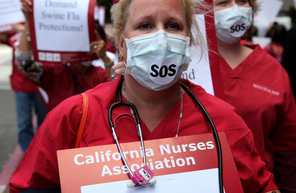A nurse wears a surgical mask during a protest outside of the University of California San Francisco medical center August 5, 2009 in San Francisco, California. The California Nurses Association, which represents nurses working across the University of California system, had threatened a walk-out on Wednesday over contract negotiations.