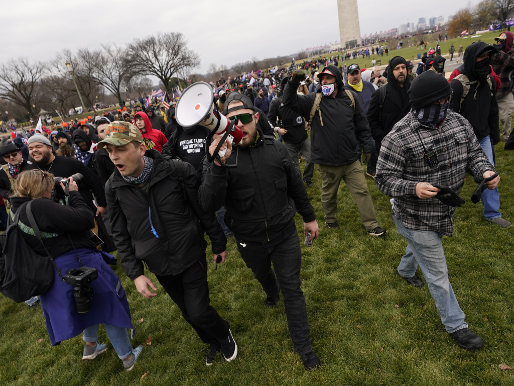 Ethan Nordean, pictured on Jan. 6 with backward baseball hat and bullhorn, leads members of the far-right group Proud Boys in marching before the riot at the U.S. Capitol. Nordean, 30, of Auburn, Washington, has described himself as the sergeant-of-arms of the Seattle chapter of the Proud Boys.