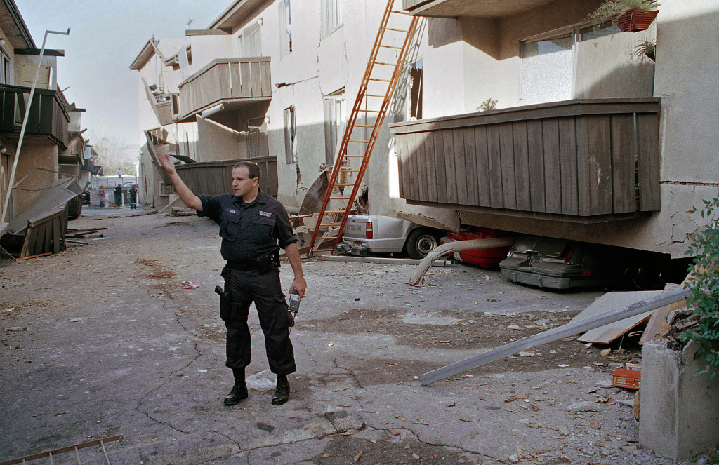 "FILE - In this Jan. 17, 1994 file photo, a Los Angeles police officer stands in front of the Northridge Meadows Apartment building, after the upper floors of the structure collapsed onto the open garages and first story, killing 16 people. Los Angeles has started the process of upgrading so-called ""soft-story"" buildings. (AP Photo/Chuck Jackson, File)"