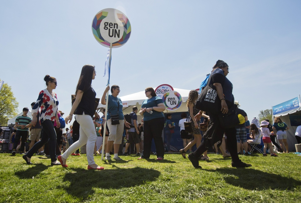 Concert attendees walk past information stands during the 2015 Earth Day concert in Washington, DC on April 18, 2015.