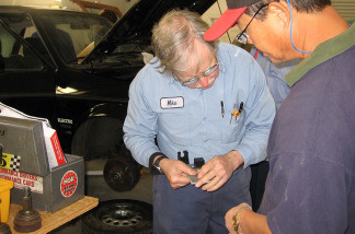 Mike Brown (left), owner of Electro Automotive, works on a gas-to-electric car conversion with a student, Daniel Marcom. Brown has been selling the parts to make such conversions since 1979.