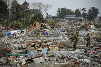 Japanese self defense personnel walk amongst a tsunami devastated town, close to the airport in Sendai on March 14, 2011.