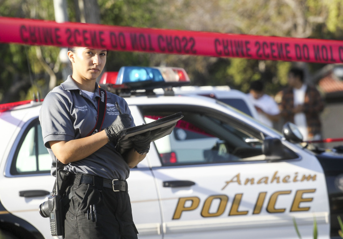 A police officer investigates the scene near Pearson Park in Anaheim, California, after three counter-protesters were stabbed while clashing with Ku Klux Klan members staging a rally.
