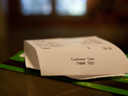 A receipt rests on top of a credit card.