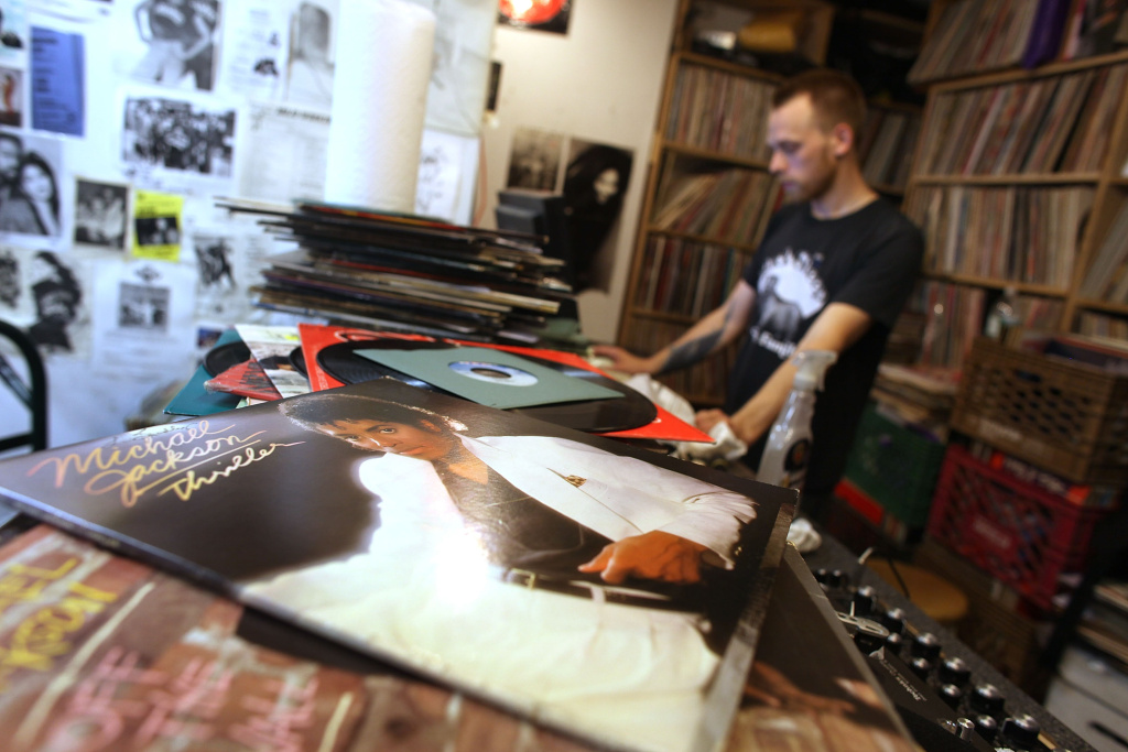 With a Michael Jackson album displayed on the counter, employee Daniel Auster spins records inside A-1 Records on June 26, 2009 in New York, New York.