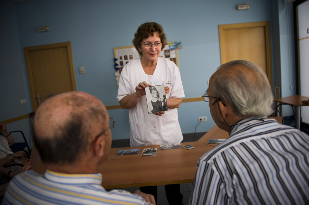 Social worker Nuria Casulleres shows a portrait of Audrey Hepburn to elderly men during a memory activity at an elderly home specializing in Alzheimer patients.