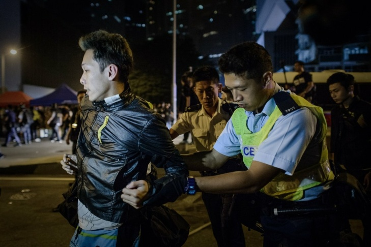 Police force arrest a pro-democracy protester in Hong Kong