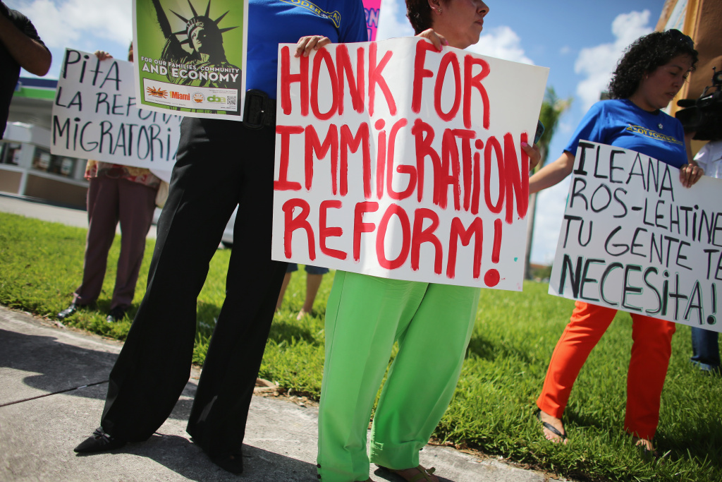 Protesters stand together as they hold a protest to ask their congress people to make immigration reform a reality on August 16, 2013 in Miami, Florida.