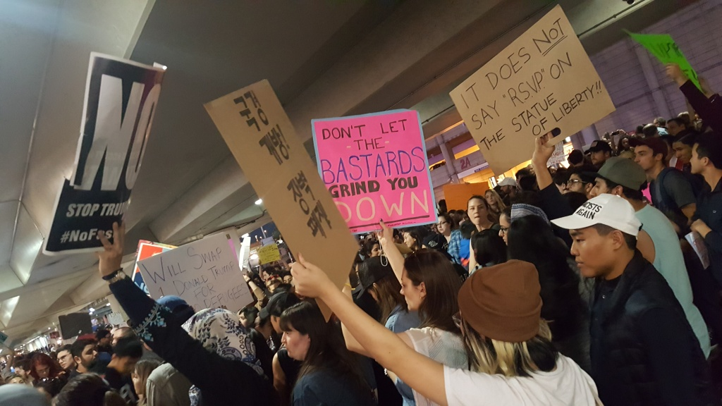 FILE: Protesters hold signs outside Terminal 2 at Los Angeles International Airport on Sunday, Jan. 29, 2017, amid calls to release immigrants detained under President Trump's then travel ban affecting majority-Muslim nations.