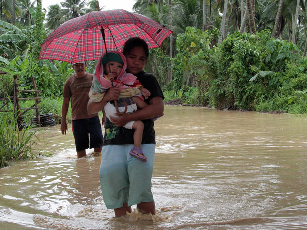 A woman carries a child through a flooded road on the island of Mindano.