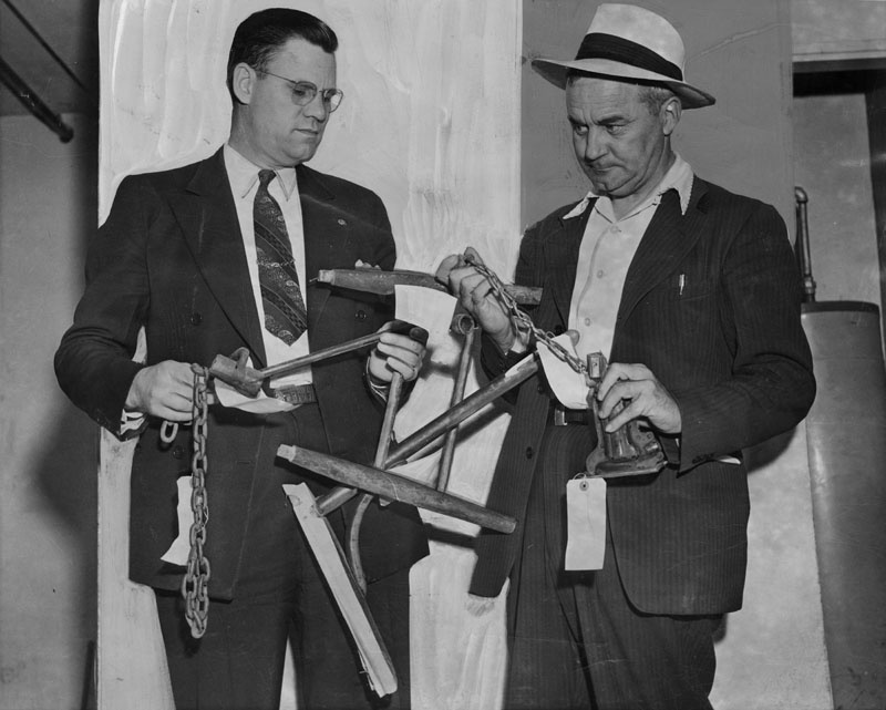 "Photograph caption dates August 3, 1942 reads, ""Weapons believed used in a bloody birthday party melee are held by Deputy Sheriffs E. M. Smith, left, and Foster Kellogg. The chains were used as flails to strike down youths, victims of the battle declared."" Photograph caption dated April 14, 1953 reads, ""Brutal weapons used in gang wars. Deputy sheriffs examine broken chairs, chains, and crowbars used by teenagers in wars without reason."" The melee referenced in the 1942 caption was tied to the death of José Gallardo Díaz."