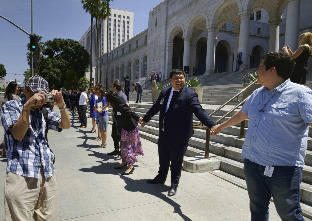 Los Angeles City Council members and others participate in a ''Hands Around City Hall'' event — a symbolic gesture of