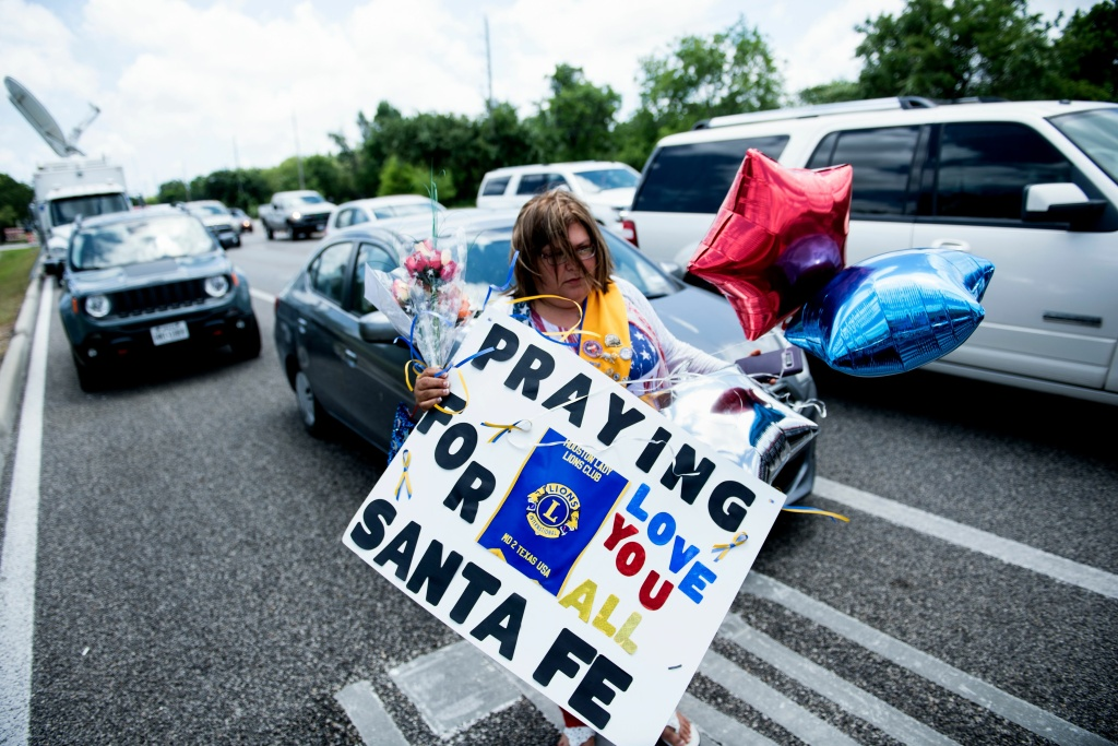 Residents bring memorial items to Santa Fe High School on May 19, 2018 in Santa Fe, Texas. Ten people, mostly students, were killed when a teenage classmate armed with a shotgun and a revolver opened fire at the school on May 18.