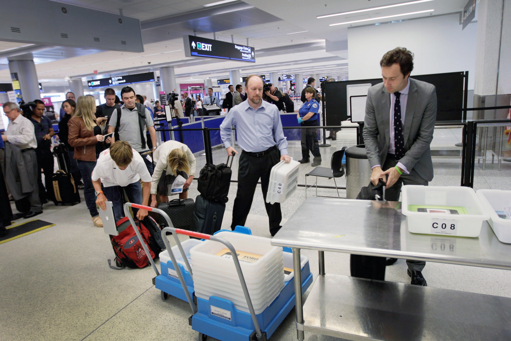 Passengers wait to clear security next to the newly opened TSA PreCheck lane which the Transportation Security Administration launched to cut down the time prescreened passengers need to stand in the traditional security line at Miami International Airport on October 4, 2011 in Miami, Florida.