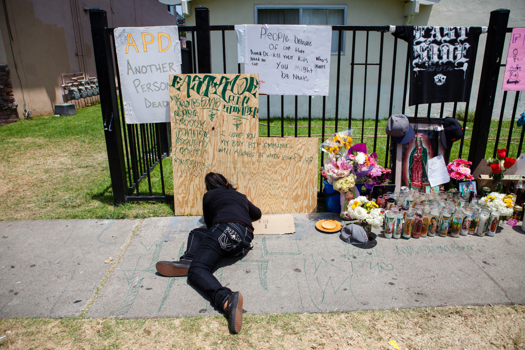 Daisy, 18, writes a message for her longtime friend, Manuel Diaz. Diaz was shot by Anaheim police on July 21, 2012.