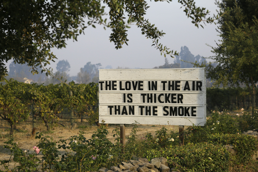 A sign about the recent wildfires stands in a vineyard outside the Cline Cellars winery Monday, Oct. 16, 2017, in Sonoma, Calif. With the winds dying down, fire crews gained ground as they battled wildfires that have devastated California wine country and other parts of the state over the past week, and thousands of people got the all-clear to return home.