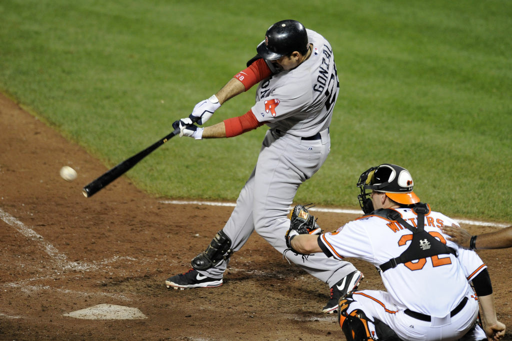 File: Boston Red Sox's Adrian Gonzalez, left, singles and drives in a run during the sixth inning of a baseball game against the Baltimore Orioles, Thursday, Aug. 16, 2012, in Baltimore. Baseball is being considered for the 2020 Olympic Games.