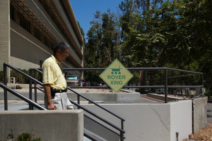 A Jet Propulsion Laboratory engineer walks past a rover crossing sign on the campus on Thursday, July 2.