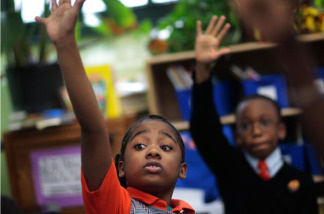 Third grade students Tyler Smalls (L) and Sekou Cisse raise their hands in reading comprehension class at Harlem Success Academy, a free, public elementary charter school March 30, 2009 in the Harlem neighborhood of New York City.