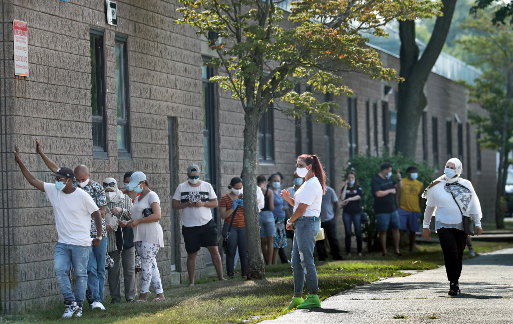 People wait in the shade while in line to get Covid-19 tests in Revere, MA.