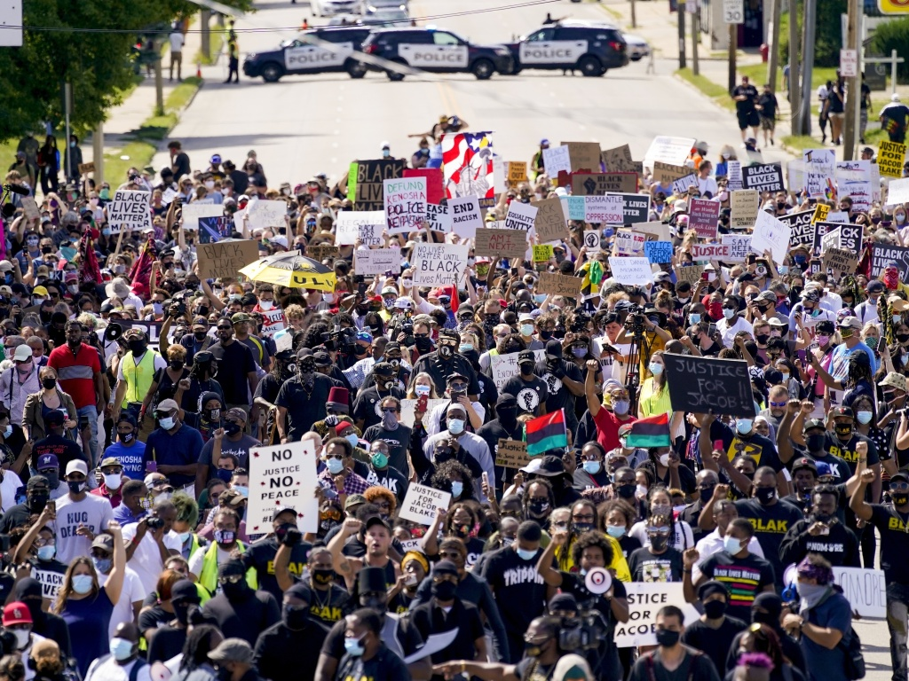 Demonstrators march at a rally Saturday for Jacob Blake in Kenosha, Wis. Officials lifted a nightly curfew on Wednesday, saying recent protests had been relatively peaceful.